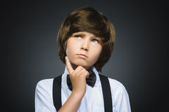 Doubt, expression and people concept - boy thinking over gray background Stock Image