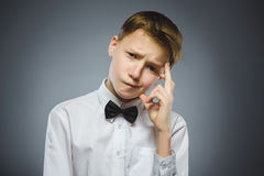 Doubt, expression and people concept - boy thinking over gray background royalty free stock images