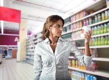 Doubt about food. Girl at supermarket with doubt about food royalty free stock photography