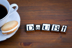 Doubt text on a wooden background. Coffee with a tasty and sweet biscuits Royalty Free Stock Photo
