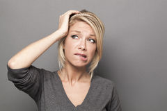 Doubt and worry concept for anxious 20s blond woman. Doubt and worry concept - anxious 20s cute blond woman expressing suspicion and anxiety with hand touching royalty free stock photo