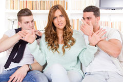 Doubtful beautiful woman hasitates between two young guys Royalty Free Stock Image