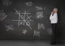 Doubtful businessman looking at tic-tac-toe Royalty Free Stock Image