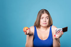Doubtful chubby lady holding apple and chocolate Royalty Free Stock Photo