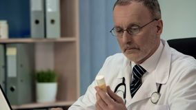 Doubtful doctor looking at pills, counterfeit poor quality medicines, placebo stock photo