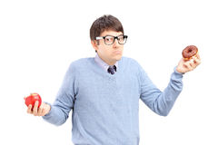 Doubtful guy holding an apple and donut Stock Images
