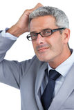 Doubtful handsome businessman wearing glasses Stock Image