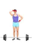Doubtful male athlete standing behind a barbell Royalty Free Stock Images