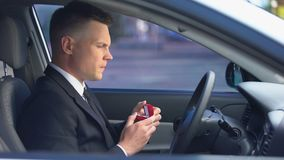 Doubtful male holding box with engagement ring sitting in car, feeling unsure. Stock footage stock footage