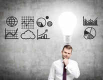 Doubtful man and light bulb with graphs Stock Image