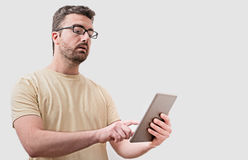Doubtful man looking at his digital tablet. On gray background Royalty Free Stock Images