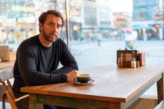 Doubtful middle aged caucasian male sitting at the table in coffee shop royalty free stock photo
