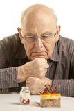 Doubtful senior man. Looking at a cake and a bottle of pills Royalty Free Stock Photography