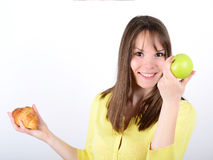 Doubtful woman holding an apple and croissant made right choice Stock Images
