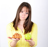 Doubtful woman holding an apple and croissant trying to decide w stock photo
