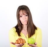 Doubtful woman holding an apple and croissant trying to decide w Royalty Free Stock Photography