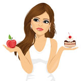 Doubtful woman holding an apple and dessert Stock Images