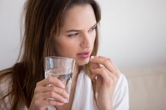 Doubtful woman holding pill and glass of water taking medicine. Doubtful sick ill young woman holding pill and glass of water taking painkiller medicine drugs to stock image