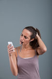 Doubtful woman looking mobile phone Royalty Free Stock Photos