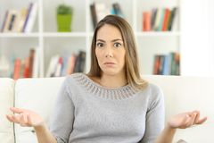 Doubtful woman shrugging shoulders at home. Front view of a doubtful woman shrugging shoulders and looking at you sitting on a sofa at home Stock Photos