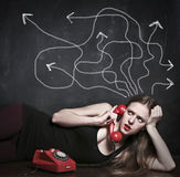 Doubtful woman using a phone Royalty Free Stock Photo