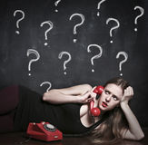 Doubtful woman using a phone Royalty Free Stock Photos