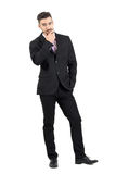 Doubtful young business man with hand on his chin looking at camera. Royalty Free Stock Photos
