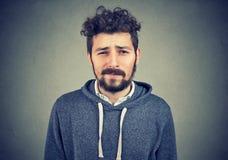 Doubtful young hipster man looking at camera stock image