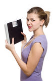 Doubtful young woman holding a weight scale royalty free stock images