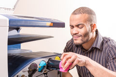 Doubting african man fixing copier in the office Stock Photography
