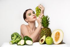 Doubting beautiful brunette girl with bright make up, with fruits and vegetables on the table. Fitness, diet, health and stock images