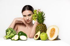 Doubting beautiful brunette girl with bright make up, with fruits and vegetables on the table. Fitness, diet, health and royalty free stock images