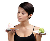 Doubting between cake and broccoli Stock Images