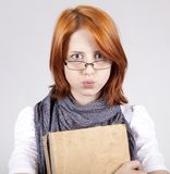 Doubting fashion girl in glasses with old book Royalty Free Stock Photo