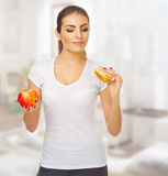 Doubting girl with apple and hamburger Stock Image