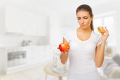 Doubting girl with apple and hamburger at light room Royalty Free Stock Photos
