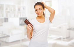 Doubting girl with chocolate at light room Royalty Free Stock Photography