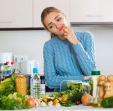 Doubting girl thinking what to cook for dinner Stock Image