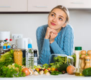 Doubting girl thinking what to cook for dinner Stock Images