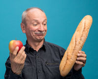 Doubting man with apple and baguette Stock Photo