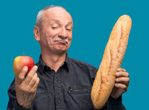 Doubting man with apple and baguette Royalty Free Stock Photography