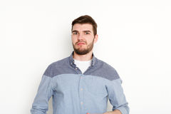 Doubting man looking at camera, isolated. Young man skeptic with unbeliever look portrait, white background Royalty Free Stock Images