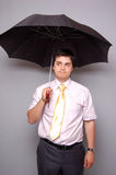 Doubting men with tie under umbrella Royalty Free Stock Image