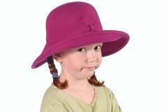 Doubting Redhead In Pink Hat. 6 year old girl with a doubting expression, wearing a green shirt and large brimmed pink hat.  In studio Royalty Free Stock Photography