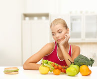 Doubting woman with fruits and hamburger Royalty Free Stock Images
