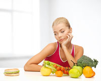 Doubting woman with fruits and hamburger Royalty Free Stock Photo