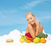 Doubting woman with fruits and hamburger Royalty Free Stock Image