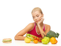 Doubting woman with fruits and hamburger Stock Photo