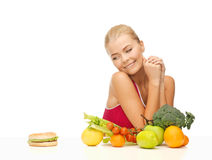 Doubting woman with fruits and hamburger Stock Photography