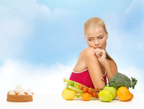 Doubting woman with fruits and pie Royalty Free Stock Photography